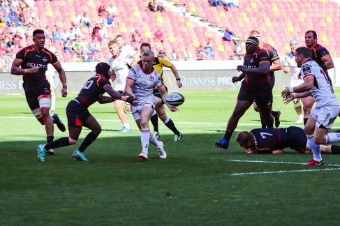 David Shanahan offloads the ball to his Ulster teammate as Masixole Banda closes in for the tackle.