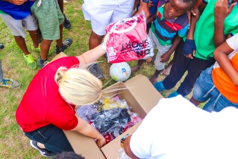 Aimee de la Harpe, from KFC in Port Elizabeth, hands out the jerseys to the children from Lakenati United FC. Photo: Stephen Kisbey-Green