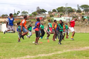 The Lakenati players, lead by Mandelake Klaas (right) warm up for their practice after receiving their kit from KFC. Photo: Stephen Kisbey-Green