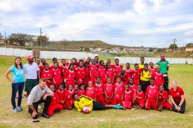 The founders, sponsors and players of the Lakhenathi United FC pose together resplendent in their new kit from KFC. Bloss Murray (Back left), Unati Snam (co-founder, second from left), Themba Faltein (coach, third from left), Mandelake Klaas (co-founder, third from right) Simthobele Twani (coach, back right), Darryl van der Berg (KFC Assistant marketing manager, kneels no left), Aimee de la Harpe (KFC Marketing Manager, kneeling right). Photo: Stephen Kisbey-Green
