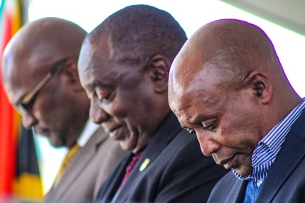 Minister Nathi Mthethwa (left), President Cyril Ramaphosa (middle), and Eastern Cape Premier Phumulo Masualle bow their heads in reverence during the moment of silence for all those lost in the recent floods and tropical storms in Southern Africa. Photo: Stephen Kisbey-Green