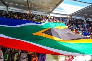 A giant South African flag was sent over the crowd as the President walked into the tent. Photo: Stephen Kisbey-Green
