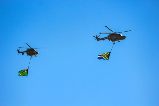 Two helicopters carrying the Flag of the President of South Africa (Left) and the South African National Flag fly over the military proceedings at Miki Yili stadium. Photo: Stephen Kisbey-Green