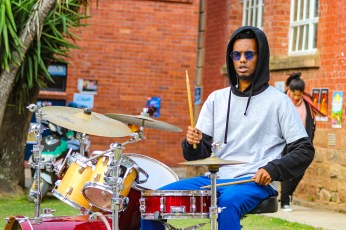 The drummer as part of a group of buskers at the Village Green plays on through the start of some heavy wind and rain. Photo: Stephen Kisbey-Green