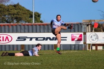 The windy conditions forced both sets of kickers to have a support player holding the ball before a conversion attempt. Here, Hannah Heskin looks on as Leah Reilly attempts the conversion. Photo: Stephen Kisbey-Green